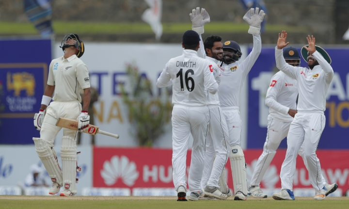 New Zealand's Jeet Raval, left, leaves after being dismissed as Sri Lankan team members celebrate during the third day of the first test cricket match between Sri Lanka and New Zealand in Galle, Sri Lanka, Friday, Aug. 16, 2019. (AP Photo/Eranga Jayawardena)