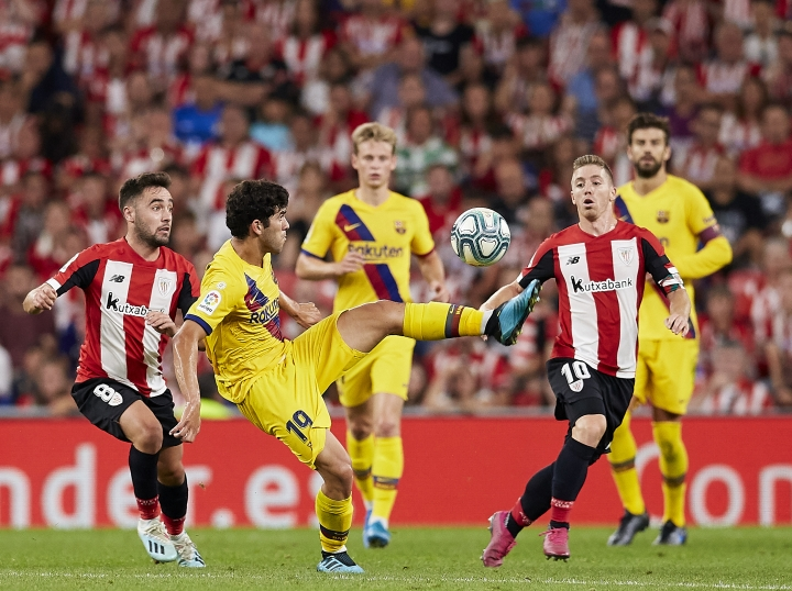 Barcelona's Carles Alena controls the ball next to Athletic Bilbao's Unai Lopez, left, and Athletic Bilbao's Iker Muniain during the Spanish La Liga soccer match between Athletic Bilbao and FC Barcelona at San Mames stadium in Bilbao, northern Spain, Friday, Aug. 16, 2019. (AP Photo/Ion Alcoba Beitia)