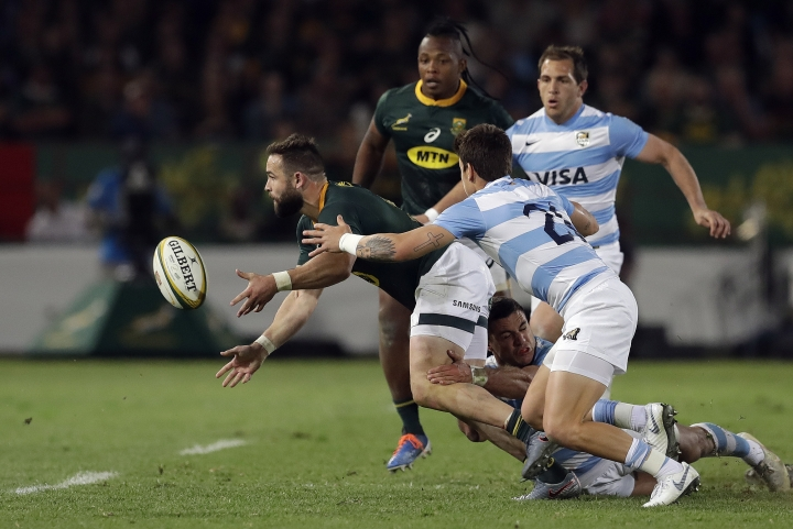 South Africa's Cobus Reinach, left, passes the ball as he avoids a tackle from Argentina's Julian Montoya, bottom, during the Rugby Championship match between South Africa and Argentina at Loftus Versfeld in Pretoria, South Africa, Saturday, Aug. 17, 2019. (AP Photo/Themba Hadebe)