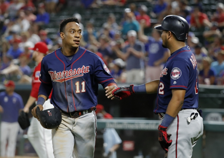 Minnesota Twins' Jorge Polanco (11) and Luis Arraez (2) celebrate after Polanco scored during the eighth inning of the team's baseball game against the Texas Rangers in Arlington, Texas, Saturday, Aug. 17, 2019. (AP Photo/Tony Gutierrez)