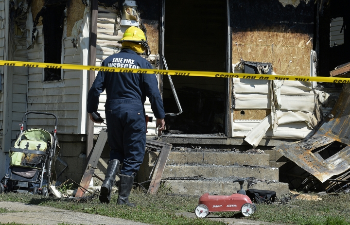 Erie Bureau of Fire Inspector Mark Polanski helps investigate a fatal fire at 1248 West 11th St. in Erie, Pa, on Sunday, Aug. 11, 2019. Authorities say an early morning fire in northwestern Pennsylvania claimed the lives of multiple children and sent another person to the hospital. (Greg Wohlford/Erie Times-News via AP)