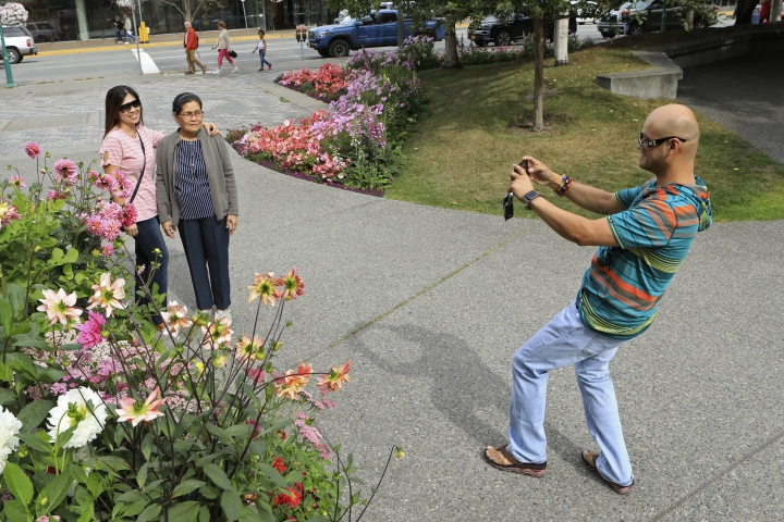 Junar Lim takes photos of Ziah Lim, left, and Arsenia Lim, all of Cavite, the Philippines, at gardens in Town Square in Anchorage, Alaska, Thursday, Aug. 15, 2019. Alaska recorded its warmest month ever in July and hot, dry weather has continued in Anchorage and much of the region south of the Alaska Range. (AP Photo/Dan Joling)
