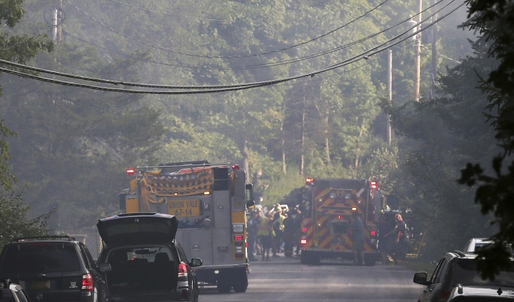 Police close off a smoke filled road as rescue workers respond to a plane that crash into a house in Union Vale, N.Y., Saturday, Aug. 17, 2019. The Federal Aviation Administration says three people were on the plane. (Frank Becerra Jr./The Journal News via AP)