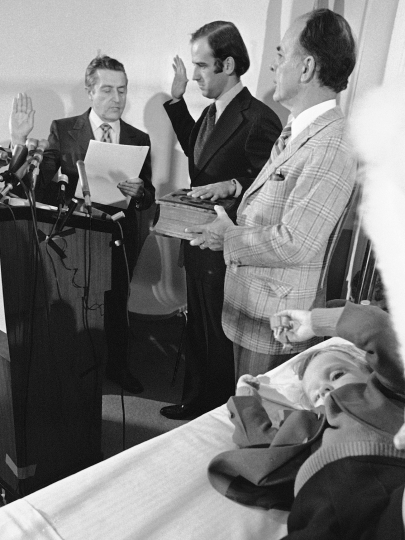 FILE - In this Jan. 5, 1973 file photo, four-year-old Beau Biden, foreground, plays near his father, Joe Biden, center, being sworn in as the U.S. senator from Delaware, by Senate Secretary Frank Valeo, left, in ceremonies in a Wilmington hospital. Beau was injured in an accident that killed his mother and sister in December 1972. Biden's father, Robert Hunter, holds the Bible. (AP Photo/File)