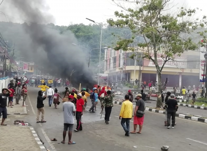People gather on a street as smoke billows from a burning car during a violent protest in Manokwari, Papua province, Indonesia, Monday, Aug. 19, 2019. The protest was sparked by accusations that Indonesian police who backed by the military, have arrested and insulted dozens of Papuan students in their dormitory in East Java's cities of Surabaya and Malang a day earlier. (AP Photo/Safwan Ashari Raharusun)
