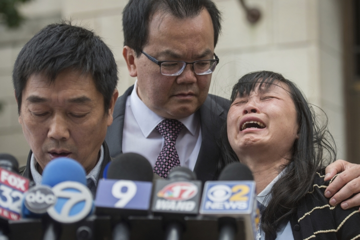 FILE - In this Monday, June 24, 2019 file photo, Lifeng Ye, the mother of slain University of Illinois scholar Yingying Zhang, cries out in grief as her husband Ronggao Zhang, left, addresses the media after a jury found Brendt Christensen guilty of Yingying Zhang's murder, at the U.S. Federal Courthouse in Peoria, Ill. Consoling her is family friend Dr. Kim Tee, center. Zhang's parents are giving $20,000 to the people who provided information that led to the arrest and conviction of their daughter's killer. (Matt Dayhoff/Journal Star via AP, File)