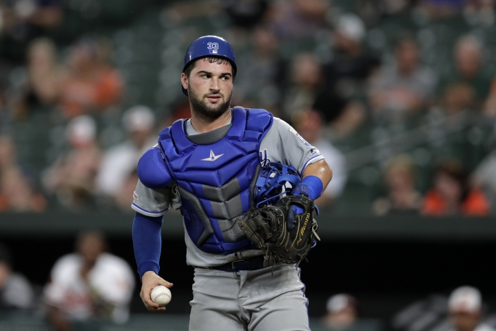 Kansas City Royals catcher Nick Dini holds a baseball between Baltimore Orioles batters during the third inning of a baseball game, Monday, Aug. 19, 2019, in Baltimore. Dini hit his first career home run and the Royals won. (AP Photo/Julio Cortez)
