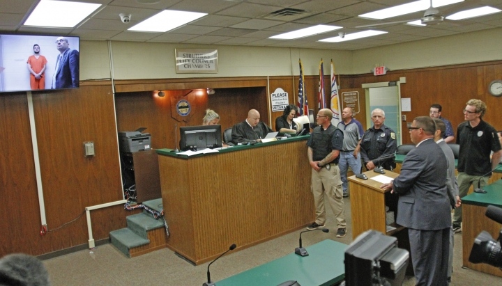 James Reardon, of New Middletown, Ohio, upper left, stands with attorney Walter Richie at the jail, seen on the video arraignment for Reardon at Struthers Municipal Court in Struthers, Ohio, Monday, Aug. 19, 2019. Reardon pleaded not guilty Monday to threatening a Jewish community center in a video that authorities say showed him shooting a semi-automatic rifle. (Robert K. Yosay/The Vindicator via AP)