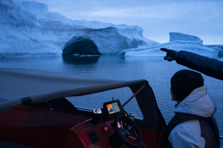 In this Aug. 16, 2019, photo, a boat navigates at night next to a large iceberg in eastern Greenland. Summer 2019 is hitting Greenland hard with record-shattering heat and extreme melt. Scientists estimate that by the end of the summer, about 440 billion tons (400 billion metric tons) of ice, maybe more, will have melted or calved off Greenland's giant ice sheet. (AP Photo/Felipe Dana)