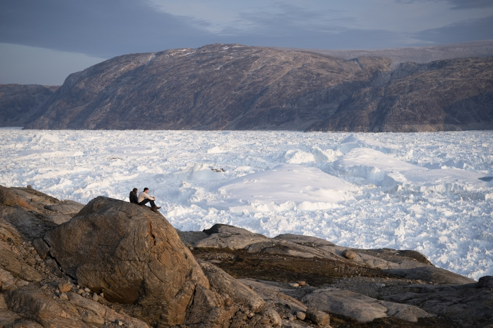 In this Aug. 16, 2019, photo, NYU student researchers sit on top of a rock overlooking the Helheim glacier in Greenland. Summer 2019 is hitting the island hard with record-shattering heat and extreme melt. Scientists estimate that by the end of the summer, about 440 billion tons of ice, maybe more, will have melted or calved off Greenland's giant ice sheet. Helheim glacier has shrunk about 6 miles (10 kilometers) since scientists visited in 2005. (AP Photo/Felipe Dana)