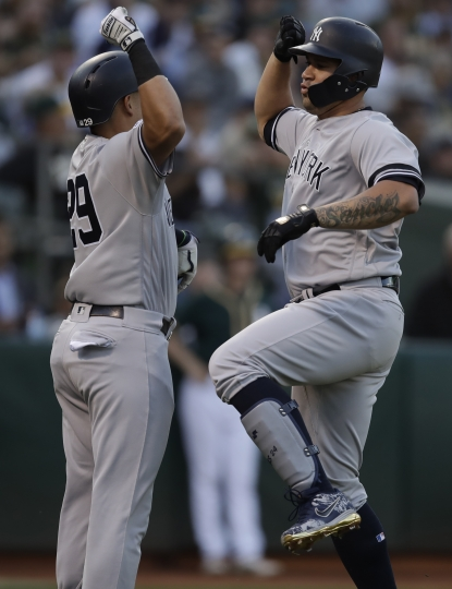 New York Yankees' Gary Sanchez, right, celebrates with Gio Urshela (29) after hitting a home run off Oakland Athletics' Homer Bailey during the first inning of a baseball game Tuesday, Aug. 20, 2019, in Oakland, Calif. (AP Photo/Ben Margot)