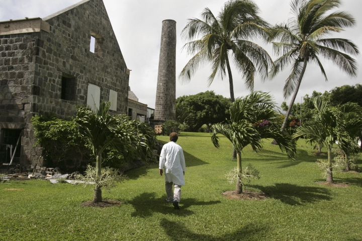 FILE - In this June 19, 2006 file photo, Yale University researcher Dr. Eugene Redmond walks on the grounds of the biomedical research center, at the site of an old sugar mill, where he spends most summers working, at Bourreu Estate on the Caribbean Island of St. Kitts. An investigation has concluded that professor Redmond sexually assaulted five students and committed sexual misconduct against at least eight others. The report by former Connecticut U.S. Attorney Deirdre Daly was released Tuesday, Aug. 20, 2019. (AP Photo/Brennan Linsley, File)