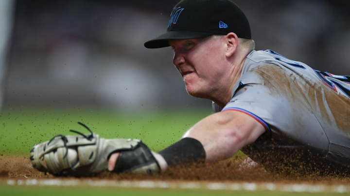 Miami Marlins first baseman Garrett Cooper dives to first base before forcing out Atlanta Braves' Adeiny Hechavarria during the sixth inning of a baseball game Tuesday, Aug. 20, 2019, in Atlanta. (AP Photo/John Amis)