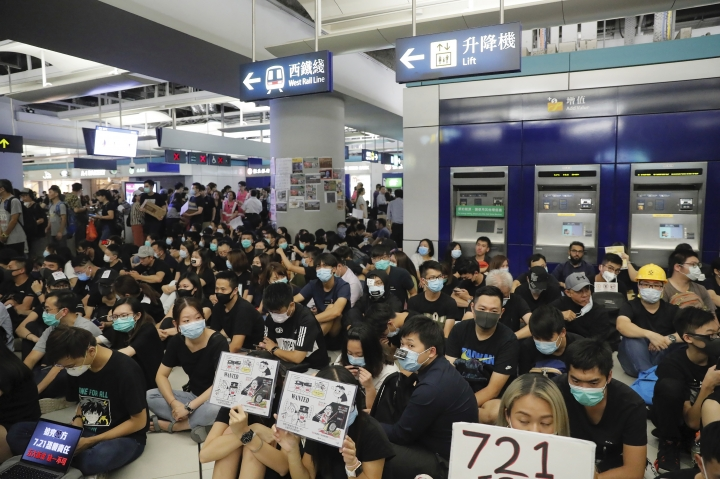 Demonstrators sit during a protest at the Yuen Long MTR station, where demonstrators and others were violently attacked by men in white T-shirts following an earlier protest in July, in Hong Kong, Wednesday, Aug. 21, 2019. Hundreds of Hong Kong protesters held a sit-in at a suburban train station to mark the anniversary of a violent attack there by masked assailants on supporters of the antigovernment movement. (AP Photo/Kin Cheung)