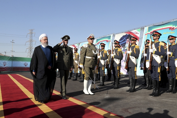 In this photo released by the official website of the office of the Iranian Presidency, President Hassan Rouhani, left, reviews an honor guard as he is accompanied by his Defense Minister Gen. Amir Hatami during a ceremony to unveil Iran-made Bavar-373 air-defense missile system, Iran, Thursday, Aug. 22, 2019. Iran says the Bavar-373 is a long-range surface-to-air missile system able to recognize up to 100 targets at a same time and confront them with six different weapons. (Iranian Presidency Office via AP)