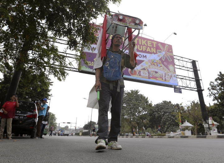 Medi Bastoni, 43, walks backwards in Bekasi, outskirt of Jakarta, Indonesia, Thursday, Aug, 22, 2019. The Indonesian man is walking over 700-kilometer (430-mile) backward from his home in eastern Java to the country's capital to draw awareness of deforestation.(AP Photo/Achmad Ibrahim)
