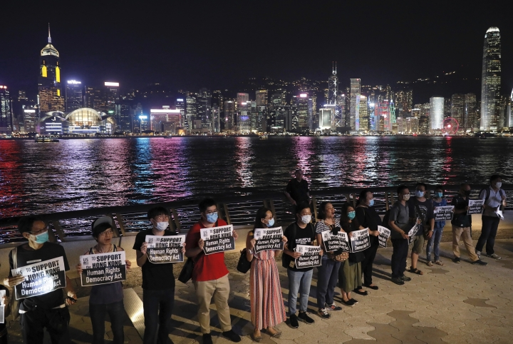 "Demonstrators hold signs as they gather at the Tsim Sha Tsui waterfront in Hong Kong, Friday, Aug. 23, 2019. Demonstrators were planning to form a 40 kilometer (25 mile) long human chain Friday night to show their resolve. They said the ""Hong Kong Way"" was inspired by the ""Baltic Way,"" when people in the Baltic states joined hands 30 years ago in a protest against Soviet control. (AP Photo/Vincent Yu)"