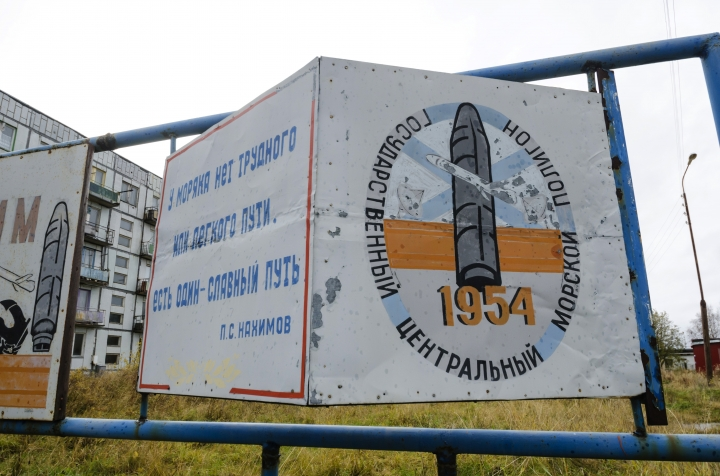 """This photo taken on Oct. 7, 2018, shows a billboard that reads """"The State Central Navy Testing Range"""" near residential buildings in the village of Nyonoksa, northwestern Russia. The Aug. 8, 2019, explosion of a rocket engine at the Russian navy's testing range just outside Nyonoksa led to a brief spike in radiation levels and raised new questions about prospective Russian weapons. (AP Photo/Sergei Yakovlev)"""