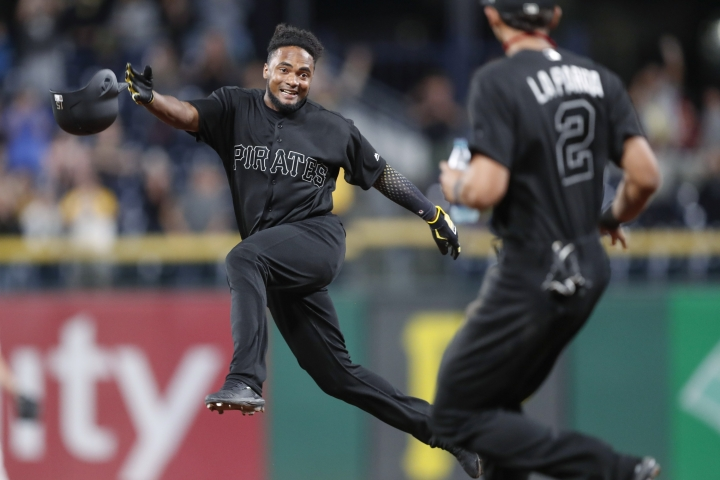 Pittsburgh Pirates' Pablo Reyes, left, leaps in the air as teammate Erik Gonzalez comes to celebrate after Reyes drove in the winning run against the Cincinnati Reds in the ninth inning of a baseball game Friday, Aug. 23, 2019, in Pittsburgh. The Pirates won 3-2. (AP Photo/Keith Srakocic)