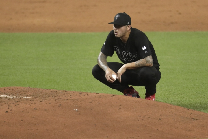 Philadelphia Phillies starting pitcher Vince Velasquez kneels on the mound after hitting Miami Marlins third baseman Brian Anderson with a pitch with the bases loaded during the third inning of a baseball game, Friday, Aug. 23, 2019, in Miami. (AP Photo/Lynne Sladky)