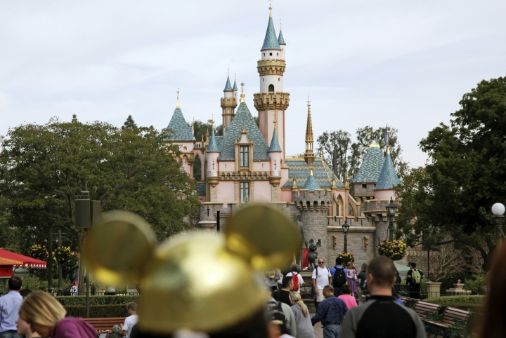 FILE - In this Jan. 22, 2015, file photo, visitors walk toward Sleeping Beauty's Castle in the background at Disneyland Resort in Anaheim, Calif. A teenage girl traveling from New Zealand to Southern California this month was infectious with highly contagious measles and may have exposed others at Disneyland and a nearby hotel, health officials said Friday, Aug. 23, 2019. (AP Photo/Jae C. Hong, File)