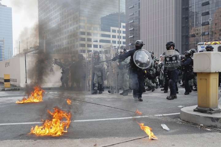"Riot police gather around small fires during a protest in Hong Kong, Saturday, Aug. 24, 2019. Chinese police said Saturday they released an employee at the British Consulate in Hong Kong as the city's pro-democracy protesters took to the streets again, this time to call for the removal of ""smart lampposts"" that raised fears of stepped-up surveillance. (AP Photo/Kin Cheung)"