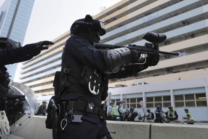 A police officer fires pepper balls during a demonstration in Hong Kong, Saturday, Aug. 24, 2019. Hong Kong protesters skirmished with police on Saturday as chaotic scenes returned to the summer-long protests for the first time in more than a week. (AP Photo/Kin Cheung)