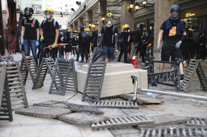 Demonstrators stand behind barricades during a protest in Hong Kong, Saturday, Aug. 24, 2019. Hong Kong protesters skirmished with police on Saturday as chaotic scenes returned to the summer-long protests for the first time in more than a week. (AP Photo/Kin Cheung)