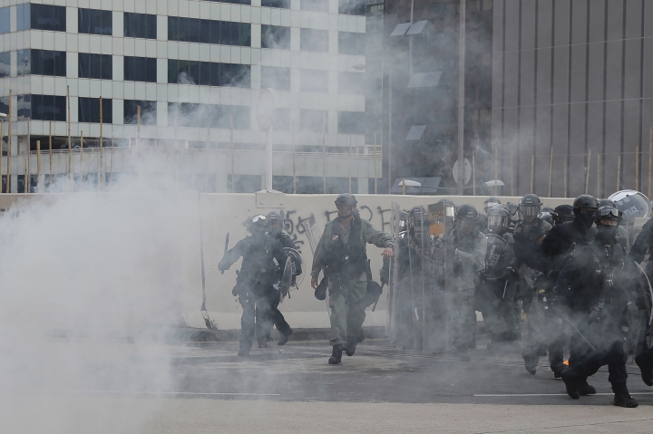 "Riot police move through a cloud of tear gas during a protest in Hong Kong, Saturday, Aug. 24, 2019. Chinese police said Saturday they released an employee at the British Consulate in Hong Kong as the city's pro-democracy protesters took to the streets again, this time to call for the removal of ""smart lampposts"" that raised fears of stepped-up surveillance. (AP Photo/Kin Cheung)"
