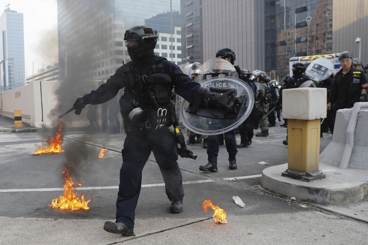 """Riot police move small fires during a protest in Hong Kong, Saturday, Aug. 24, 2019. Chinese police said Saturday they released an employee at the British Consulate in Hong Kong as the city's pro-democracy protesters took to the streets again, this time to call for the removal of """"smart lampposts"""" that raised fears of stepped-up surveillance. (AP Photo/Kin Cheung)"""