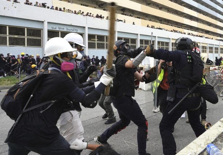 """Police and demonstrators clash during a protest in Hong Kong, Saturday, Aug. 24, 2019. Chinese police said Saturday they released an employee at the British Consulate in Hong Kong as the city's pro-democracy protesters took to the streets again, this time to call for the removal of """"smart lampposts"""" that raised fears of stepped-up surveillance. (AP Photo/Vincent Yu)"""