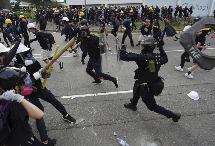 Police and demonstrators clash during a protest in Hong Kong, Saturday, Aug. 24, 2019. The protesters were part of a larger group marching to demand the removal of smart lampposts installed in a Kowloon district over fears they could contain high-tech cameras and facial recognition software used for surveillance by Chinese authorities. (AP Photo/Vincent Yu)