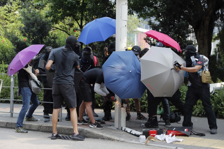 """Demonstrators use umbrellas to shield themselves from view while they try to cut down a smart lamppost during a protest in Hong Kong, Saturday, Aug. 24, 2019. Chinese police said Saturday they released an employee at the British Consulate in Hong Kong as the city's pro-democracy protesters took to the streets again, this time to call for the removal of """"smart lampposts"""" that raised fears of stepped-up surveillance. (AP Photo/Kin Cheung)"""