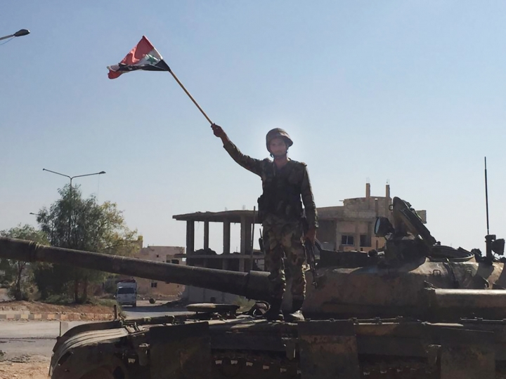 A Syrian soldier stands on a tank waving a national flag in the northwestern town of Khan Sheikhoun, Syria, on Saturday, Aug. 24, 2019. The town was captured by Syrian troops this week after a monthslong offensive. (AP Photo/Albert Aji)