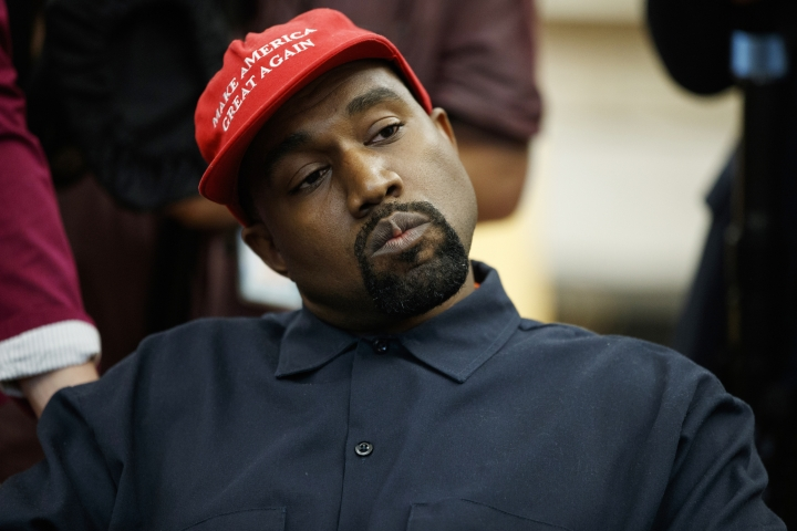FILE - In this Oct. 11, 2018, file photo rapper Kanye West listens to a question from a reporter during a meeting in the Oval Office of the White House with President Donald Trump in Washington. On Sunday, Aug. 25, 2019, Kanye West hosted a Sunday Service in Ohio in support of those affected by the recent mass shooting. A large crowd gathered at the service in a park in Dayton. (AP Photo/Evan Vucci, File)