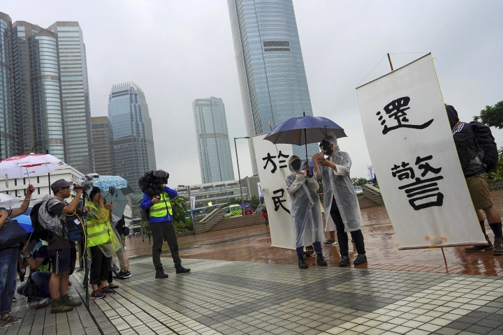 "Reporters film a participant wearing a raincoat speaks next to a banners reads ""The duty fulfill by the police belong to the people"" as they take part in a rally to support the Hong Kong's Police at Edinburgh Place in Hong Kong, Sunday, Aug. 25, 2019. (AP Photo/Vincent Yu)"