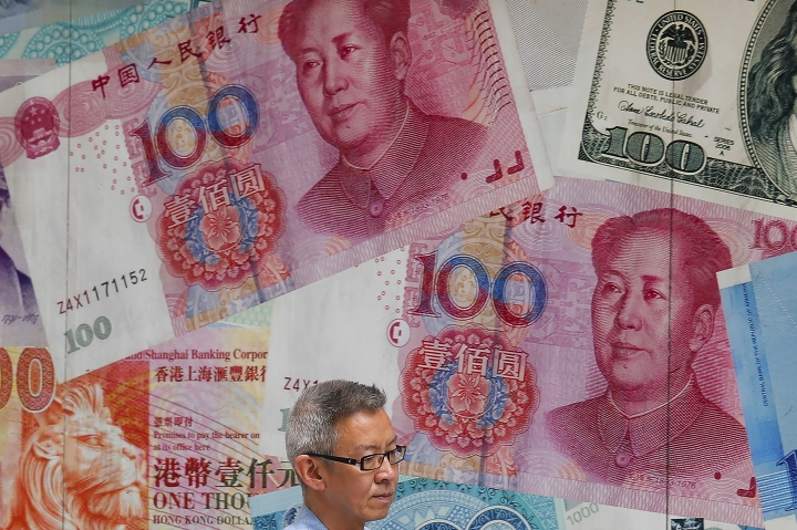 FILE - In this Aug. 6, 2019, file photo, a man walks by a money exchange shop decorated with Chinese yuan banknotes and other countries currency banknotes at Central, a business district in Hong Kong. China allowed its yuan to sink to an 11-year low against the dollar after U.S. President Donald Trump threatened to block American companies from doing business with this country. The yuan declined Monday, Aug. 26, 2019 to 7.1468 to the dollar, its weakest rate since January 2008. (AP Photo/Kin Cheung, File)