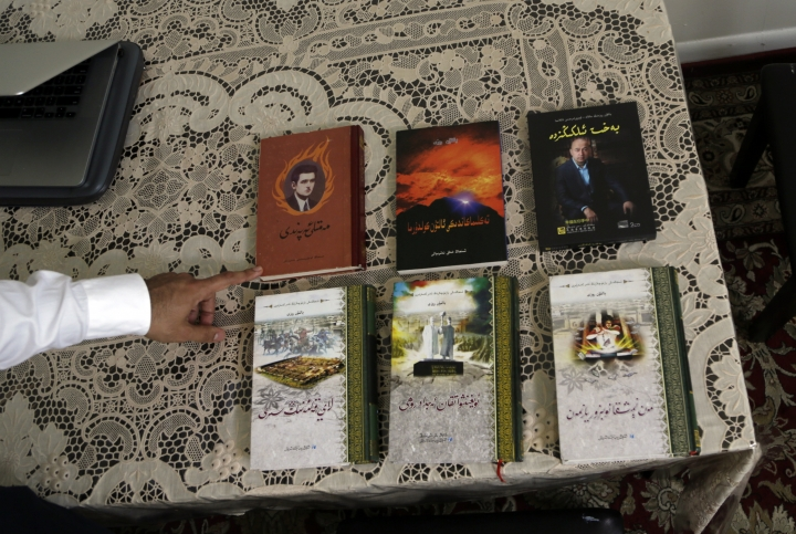 Kamalturk Yalqun displays material written by his father, Rozi, Thursday, April 18, 2019, in Philadelphia. Rozi was well-accustomed to dealing with the Chinese government's fears of an independent Uighur identity, and though he sometimes quarreled with the censors, his works always made it to publication in the end. (AP Photo/Jacqueline Larma)