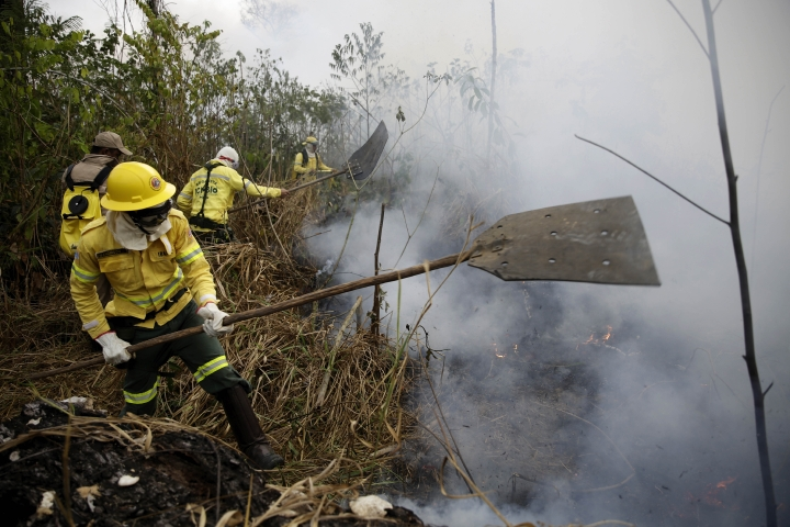 """Firefighters work to put out fires along the road to Jacunda National Forest, near the city of Porto Velho in the Vila Nova Samuel region which is part of Brazil's Amazon, Monday, Aug. 26, 2019. The Group of Seven nations on Monday pledged tens of millions of dollars to help Amazon countries fight raging wildfires, even as Brazilian President Jair Bolsonaro accused rich countries of treating the region like a """"colony."""" (AP Photo/Eraldo Peres)"""