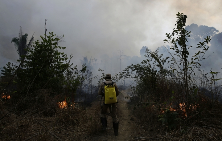 """A firefighter works to put out fires along the road to Jacunda National Forest, near the city of Porto Velho in the Vila Nova Samuel region which is part of Brazil's Amazon, Monday, Aug. 26, 2019. The Group of Seven nations on Monday pledged tens of millions of dollars to help Amazon countries fight raging wildfires, even as Brazilian President Jair Bolsonaro accused rich countries of treating the region like a """"colony."""" (AP Photo/Eraldo Peres)"""