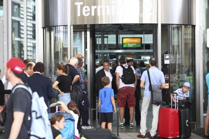 "People wait outside the Munich Airport in Munich, Germany, Tuesday, Aug. 27, 2019, after some of its terminals were closed because a person has likely entered the ""clean area"" through an emergency exit door. The international airport tweeted Tuesday morning that terminal 2 and areas B and C of terminal 1 had been closed for police operations.(AP Photo/Matthias Schrader)"