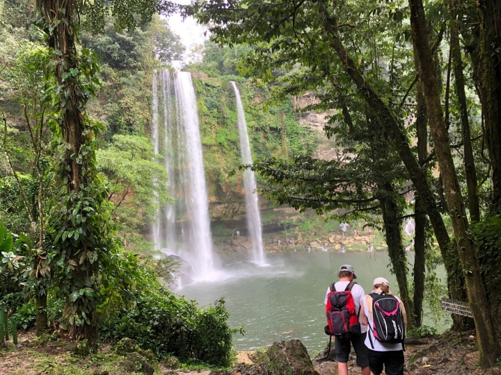This Feb. 13, 2019 photo shows two visitors at Misol Ha waterfall, tucked away in the rainforest of Chiapas state, in southern Mexico. The waterfall features a single cascade of some 115 feet (35 meters) that spills into a pool encircled by tropical greenery. (AP Photo/Anita Snow)