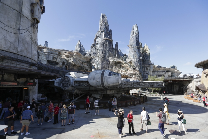 Park visitors walk near the entrance to the Millennium Falcon Smugglers Run ride during a preview of the Star Wars themed land, Galaxy's Edge in Hollywood Studios at Disney World, Tuesday, Aug. 27, 2019, in Lake Buena Vista, Fla. The attraction will open Thursday to park guests. (AP Photo/John Raoux)