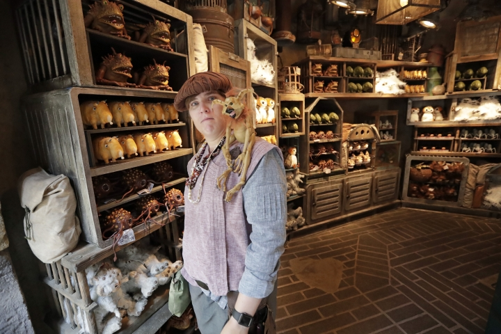 A shop keeper displays creatures that will sit on your shoulder and other merchandise for sale during a preview of the Star Wars themed land, Galaxy's Edge in Hollywood Studios at Disney World, Tuesday, Aug. 27, 2019, in Lake Buena Vista, Fla. The attraction will open Thursday to park guests. (AP Photo/John Raoux)