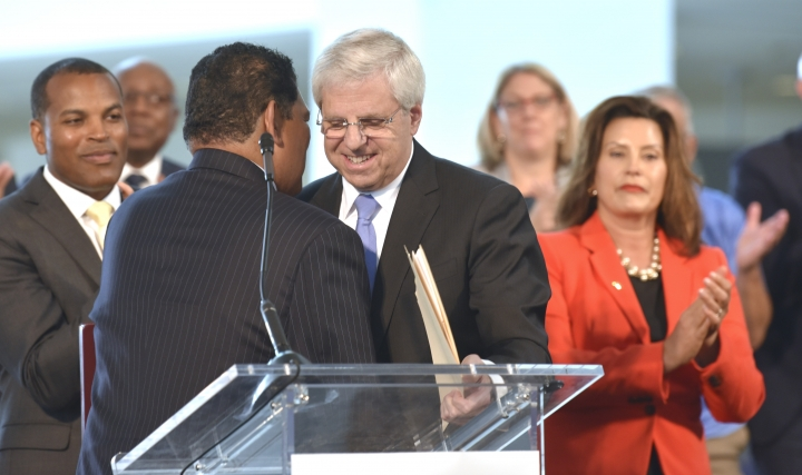 Larry Alexander, left, president and CEO of the Detroit Metro Convention and Visitors Bureau and chair of the Detroit Regional Convention Facility Authority, welcomes Gary Torgow, right, executive chairman of TCF Financial Corporation, to the podium to announce that Cobo Center is now named TCF Center, Tuesday, Aug. 27, 2019. (Todd McInturf /Detroit News via AP)