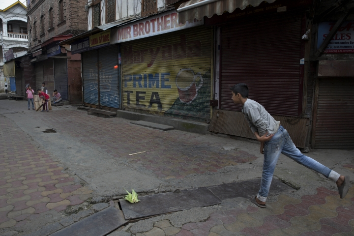 Kashmiri children play cricket outside a closed market in central Srinagar, Indian controlled Kashmir, Tuesday, Aug. 27, 2019. Earlier this month, the Indian government revoked Muslim-majority Kashmir's decades-old special status guaranteed under India's constitution. The government followed the move with an intense crackdown including a media blackout and backed by thousands of troops. (AP Photo/Dar Yasin)