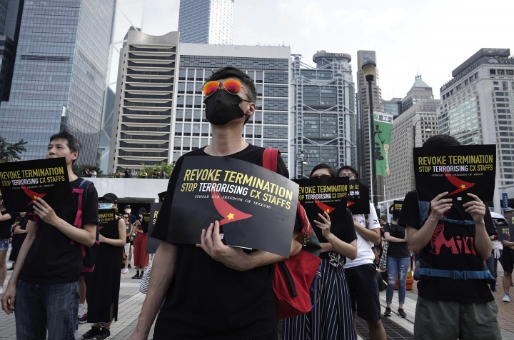 Demonstrators hold signs opposing the recent firings of Cathay Pacific employees as they gather for a demonstration in Hong Kong, Wednesday, Aug. 28, 2019. Trade union members in Hong Kong are rallying against the city's flagship Cathay Pacific airline for firing employees linked to ongoing pro-democracy protests. (AP Photo/Vincent Yu)