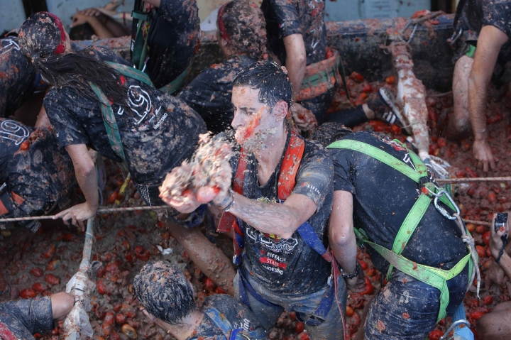 """Revellers throw tomatoes at each other during the annual """"Tomatina"""", tomato fight fiesta in the village of Bunol near Valencia, Spain, Wednesday, Aug. 28, 2019. (AP Photo/Alberto Saiz)"""
