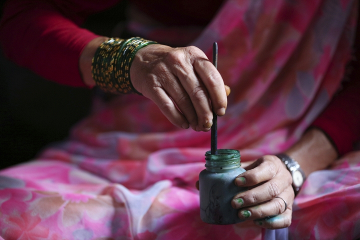 In this July 31, 2019, photo, Tej Kumari Chitrakar mixes color to make traditional paintings ahead of Naag Panchami festival at her residence in Bhaktapur, Nepal. Chitrakar families in the Nepalese capital of Kathmandu were renowned traditional painters and sculptors who depicted gods and goddesses on temples, masks of Hindu deities and posters for various religious celebrations. For Tej Kumari and her husband it is a struggle to keep the dying art alive against the modern mass produced prints. (AP Photo/Niranjan Shrestha)