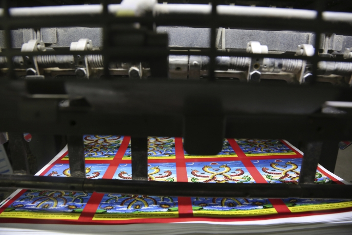 In this Aug. 2, 2019, photo, machine printed posters get ready ahead of Naag panchami festival at a printing press in Kathmandu, Nepal. The art and tradition of Nepal's Chitrakar families, who depicted gods and goddesses on temples, masks of Hindu deities and posters for various religious celebrations is dying because of mass machine printed posters and card-size pictures of gods that are cheaper and more popular. (AP Photo/Niranjan Shrestha)